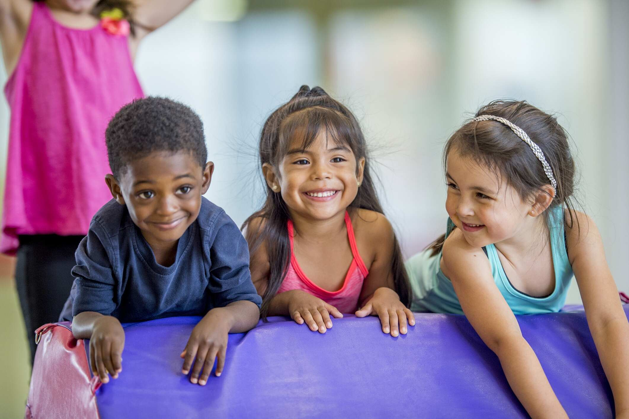 Three preschool kids are indoors in their school. They are having fun during gym class. They are leaning on a gymnastics mat and smiling together.
